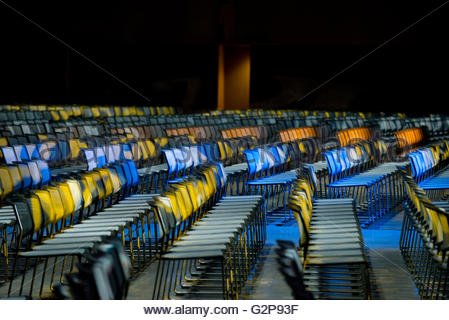 Rows of chairs set up for a business conference in auditorium at night with colored lights side view shallow depth - Stock Photo