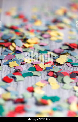 Bright multicolored Paper Confetti on Table in various shapes - Stock Photo