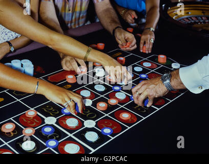 Roulette players and dealer placing chips on the table - Stock Photo