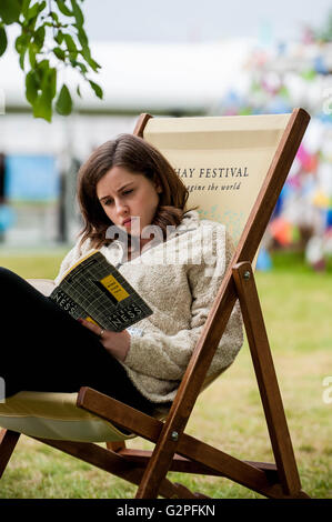 Hay on Wye, UK. Wednesday 01 June 2016 A young woman reads a book on a deckchair in the fine weather at hay  at - Stock Photo