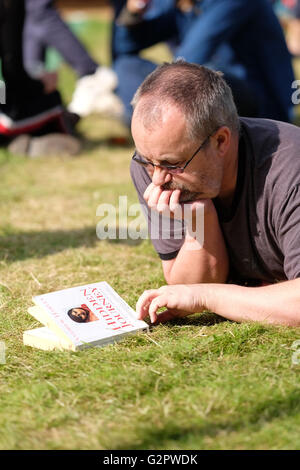 Hay Festival, Wales, UK - Thursday 2nd June 2016 -  A visitor looks at the cover of his new book on the lawns at - Stock Photo