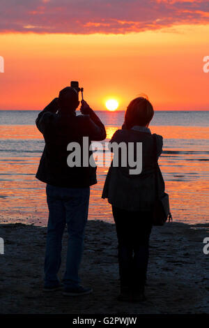 Southport, Merseyside, UK. 02nd June, 2016. A newlywed couple on their honeymoon take selfies against the setting - Stock Photo