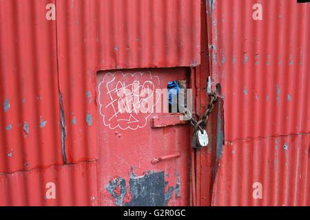 red corrugated metal door, gate with graffiti, wear, padlock, rusty chain - Stock Photo