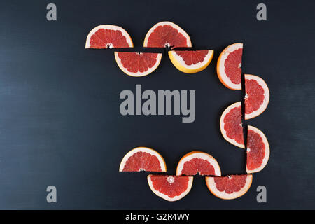 Sliced halves of red grapefruit creating a frame on black painted surface. Top view with copy space - Stock Photo