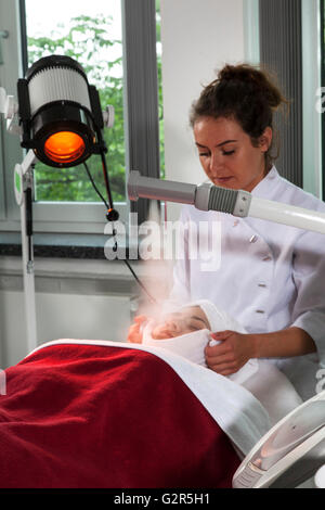 Beautician at work in a cosmetics institute - Stock Photo