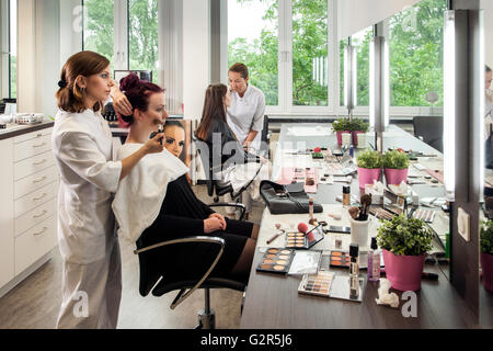 Beautician makeup a young woman. - Stock Photo