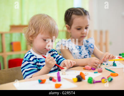 Kids or children creating arts and crafts in kindergarten - Stock Photo