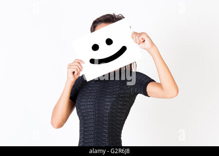 Woman in elegant dress holding smiley face paper - indicates happiness and satisfaction - Stock Photo