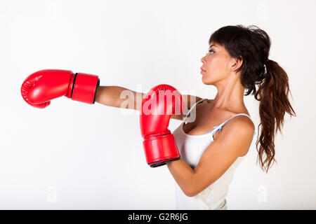 Young beautiful woman punching while wearing boxing gloves on white isolated background - fitness and power concept - Stock Photo