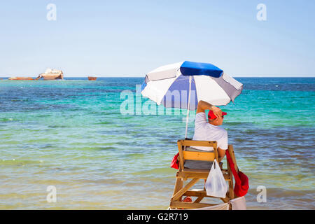 Sunny Mediterranean beach, lifeguard sitting in observation post, on background of a sunken ship in shallows. Torrevieja, - Stock Photo