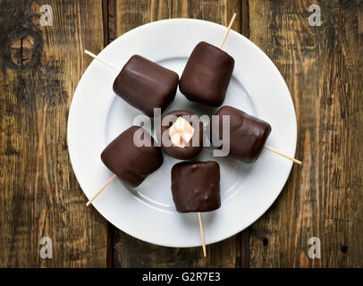 Summer dessert frozen banana covered with chocolate, top view - Stock Photo
