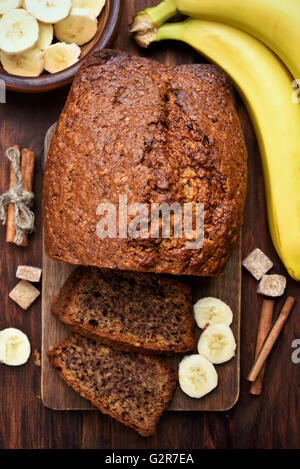Banana bread and fruits on wooden table, top view - Stock Photo