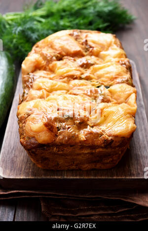 Vegetable loaf with zucchini, carrot and cheese on wooden cutting board - Stock Photo
