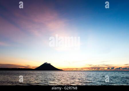 Sunset over Manado Tua, North Sulawesi, Indonesia - Stock Photo