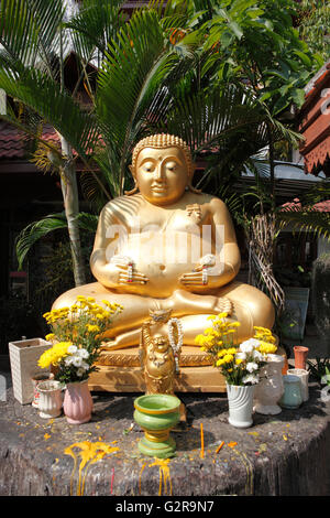 Golden Buddha statue in the garden of the Wat Phra Singha temple, Chiang Rai, Thailand, Asia - Stock Photo