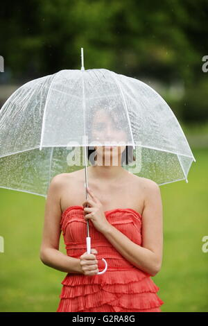Woman with umbrella outside in a summer rain, Lake Constance, Lindau - Bodensee, Bavaria, Germany - Stock Photo