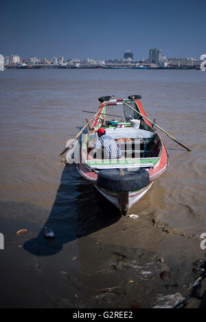 A local boat driver in his traditional Burmese boat waiting for costumers, Dala, Yangon, Myanmar. - Stock Photo