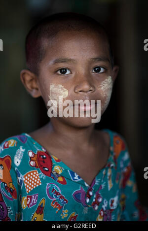 Portrait of a Burmese  young boy wearing traditional make-up (thanakha) on his face,  Dala, Yangon, Myanmar. - Stock Photo