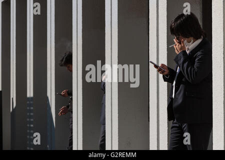 Japanese male office workers or salarymen smoke outside a building in Jimbocho, Tokyo, Japan. Friday December 18th - Stock Photo