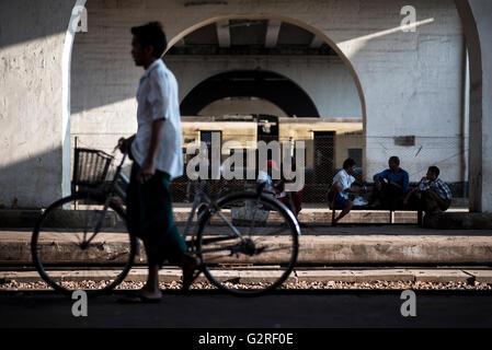 A man pushing a bike at the Yangon Central Train Station, Myanmar. - Stock Photo