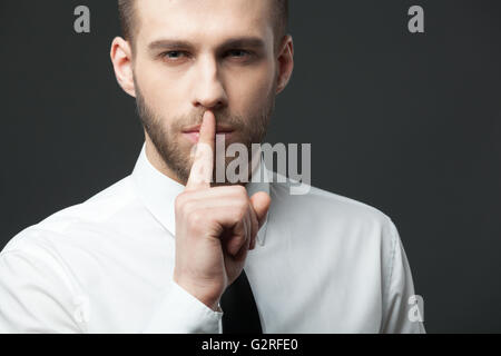 Keep your secrets! Studio portrait of young handsome businessman gesturing 'shh' to the camera. - Stock Photo