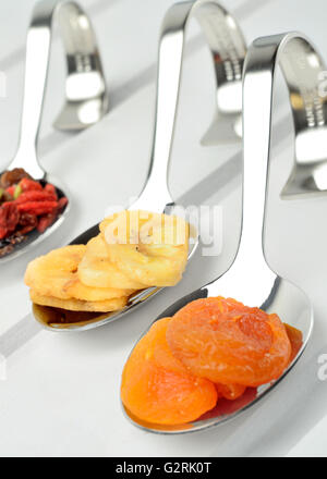 Dried fruits in a spoon on wooden table - Stock Photo