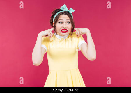 Cute irritated pinup girl in yellow dress closed her ears by fingers over pink background - Stock Photo