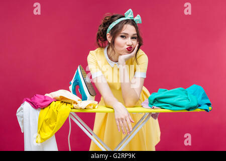 Bored sad young woman ironing clothes over pink background - Stock Photo