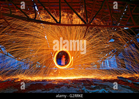 Burning Steel Wool spinning. Showers of glowing sparks from spinning steel wool in ruins - Stock Photo