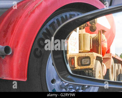 view of a concrete mixer in a side view mirror - Stock Photo