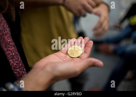 A woman holding a souvenir coin taken from one of the cathedrals visited, Paris France. - Stock Photo
