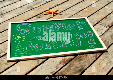 the text summer camp written with chalk of different colors in a chalkboard and a starfish on a wooden pier - Stock Photo