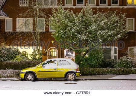 Car parked in residential neighborhood on snowy winter night, Groningen, Netherlands - Stock Photo