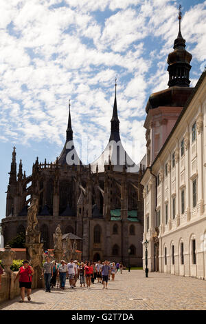 A group of tourists walking along St Barbara Street by St. Barbara's Church and the Jesuit College in Kutna Hora, - Stock Photo