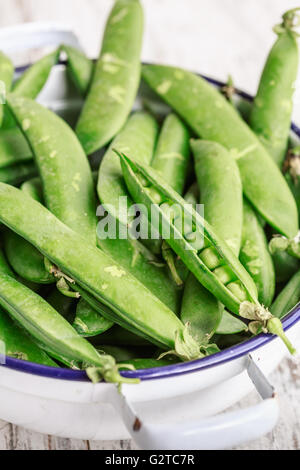 Pods of green fresh peas in a bowl - Stock Photo