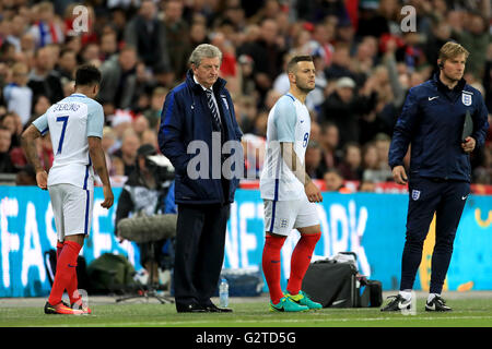 England manager Roy Hodgson (second left) looks to bring on Raheem Sterling (left) and Jack Wilshere as substitutes - Stock Photo