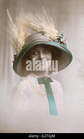 Hand-coloured sepia postcard of a beautiful Edwardian lady in a picture hat. - Stock Photo