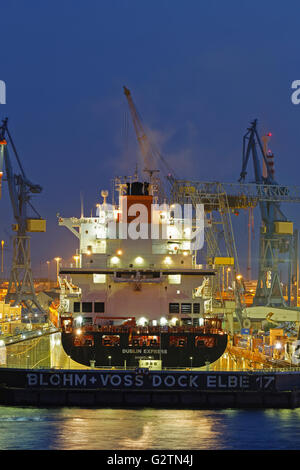 Container ship in the floating dock of Blohm and Voss, Hamburg harbor at night, Hamburg, Germany - Stock Photo