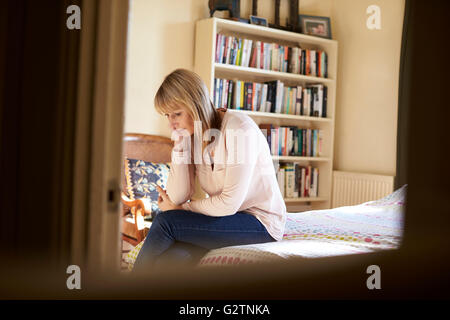 Depressed Mature Woman Sitting On Bed At Home - Stock Photo