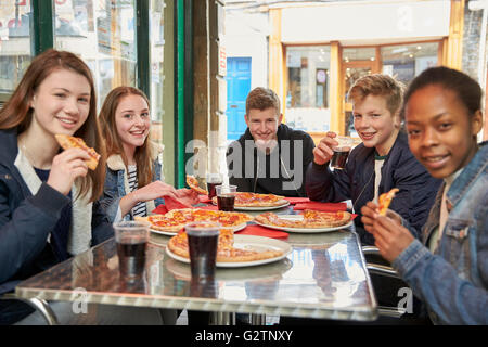 Group Of Teenagers Eating Pizza In Cafe - Stock Photo