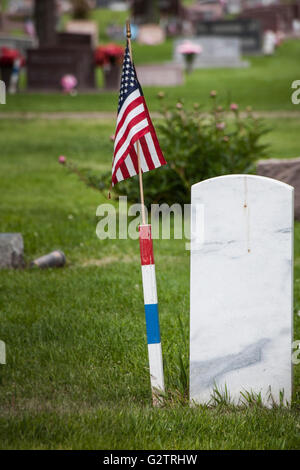 Seen from behind, a solid marble grave marker, with an American flag next to it identifying it as a military veteran's - Stock Photo