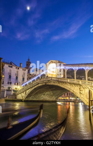 Night view of Rialto Bridge and the typical gondolas in the canal Venice Veneto Italy Europe - Stock Photo