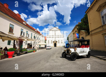 Zagreb upper town.Saint Catherine Church on the back and vintage touristic car in front - Stock Photo