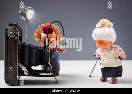 Puppets of senior photographer taking pictures of his old ladies with vintage camera in studio - Stock Photo