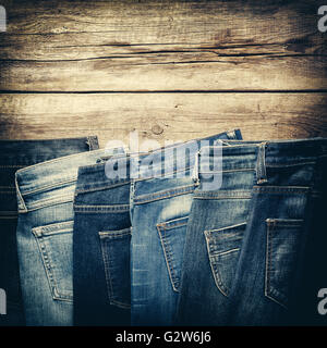 Different jeans on wooden background in store. Retro toned. - Stock Photo