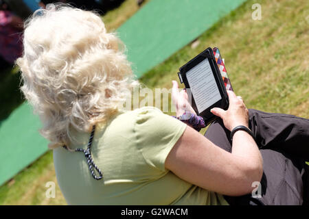 Hay Festival, Wales, UK - June 2016 -  A woman sits and reads her ebook reader tablet on the Hay Festival lawns. - Stock Photo