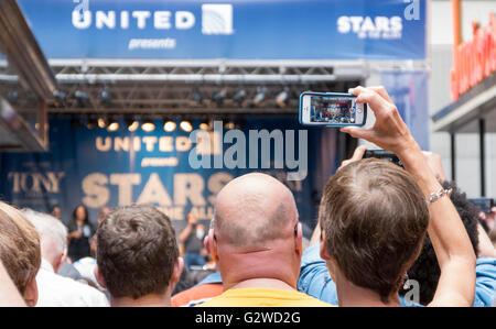 Woman recording a performance of a song by the cast of the musical The Colour Purple on her mobile phone at the - Stock Photo