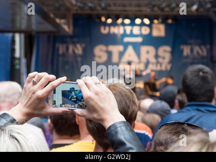 Woman recording a performance of a song from the musical Wicked on her mobile phone at the free Stars in the Alley - Stock Photo
