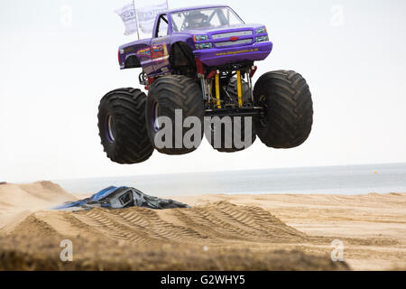 Bournemouth, Dorset UK 4 June 2016. Slingshot monster truck jumping in the air crushing cars on Bournemouth beach - Stock Photo