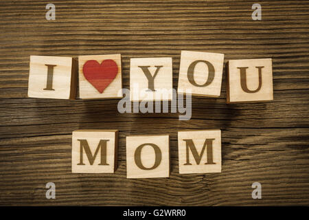 Message I LOVE YOU MOM made of letters on wooden blocks. Mothers Day. Letters and heart shape drawn by the author - Stock Photo